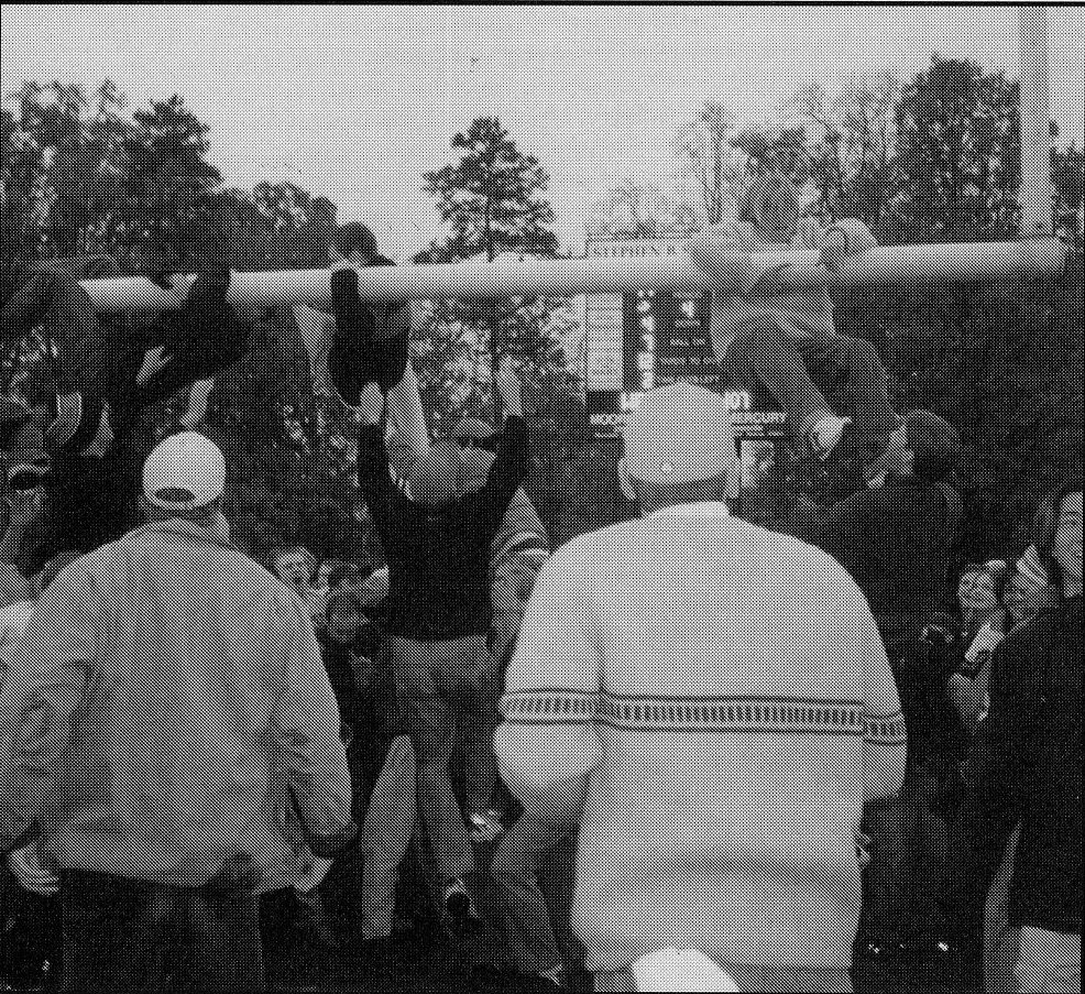 Excited Wildcat fans tear down the goalposts after the last game of the undefeated season; a few fans hang off the posts