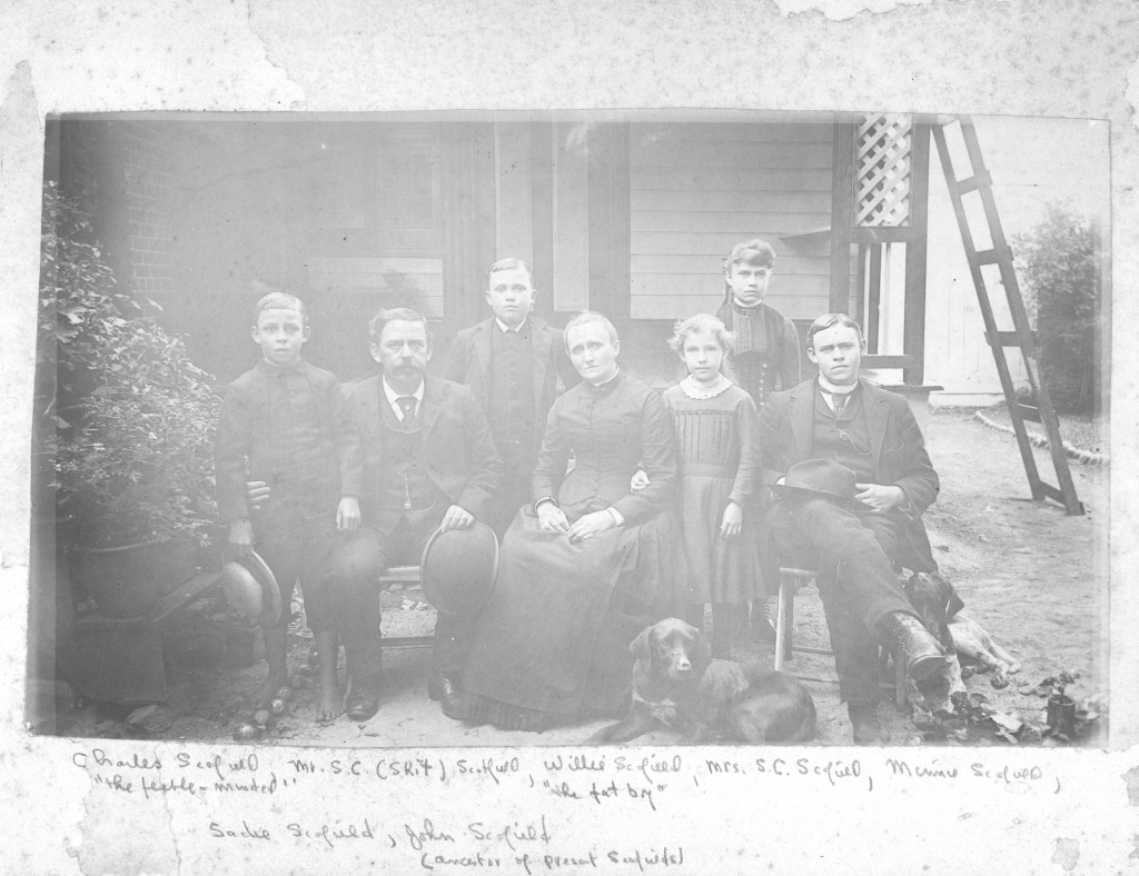 The Scofield family in front of their home. There dog is also laying in the front.