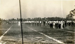 Many people standing in lines on the football field wearing black pants and white shirts