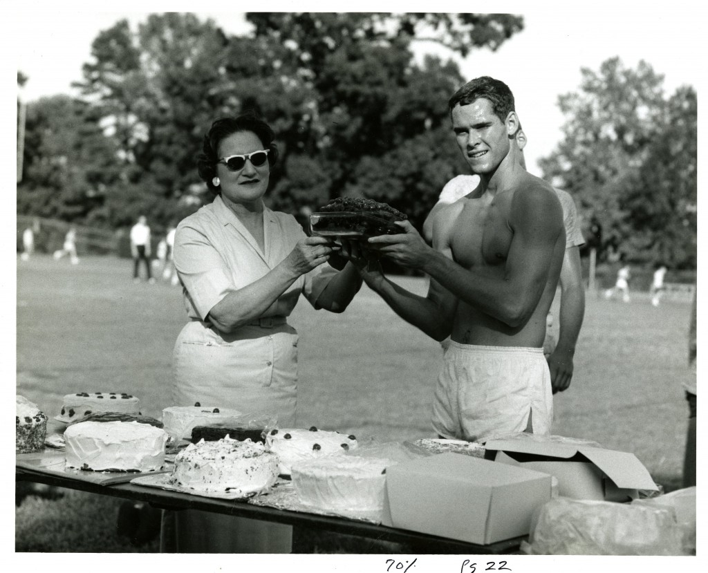 Daisy Whittle presents a cake to a winning racer(who isn't wearing a shirts) in 1963, while there is a table full of cakes right next to them and people running the the blurred background
