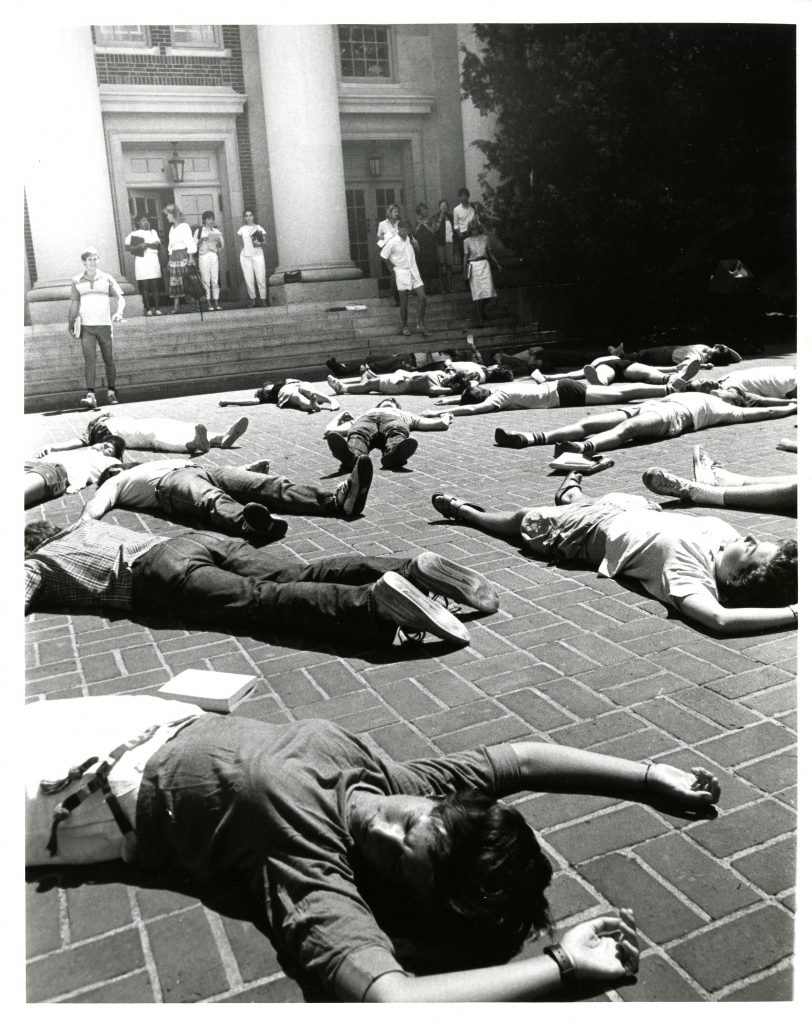 A photo capturing students participating in the die-in inf front of Chambers Building. Students lying on the ground appearing to be dead outside of chambers while other students are walking out of chambers