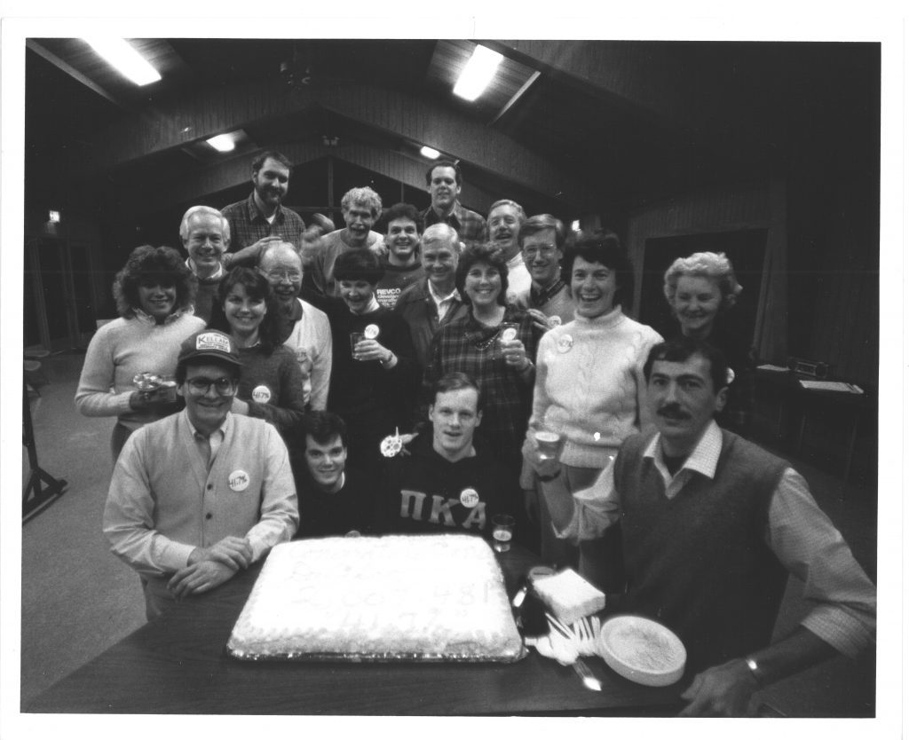 """Davidson employees gather around a cake with icing spelling out """"Congratulations Davidson, 2,007,481, 41.7%"""" at a Development retreat in 1986. Bill is seated far right, next to the cake."""