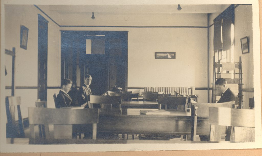 Three students at a table in the Carnegie Library (now Carnegie Guest House), circa 1916.