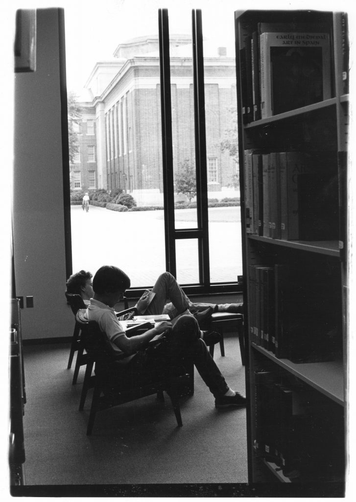 Two students study by a window on the first floor of Little Library, with Chambers visible in the background, 1980s.