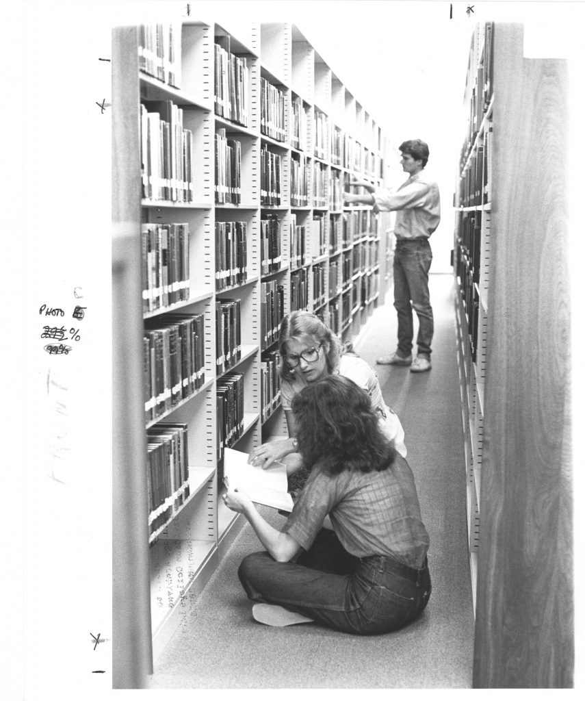 Three students work in an aisle of Little Library, circa early 1980s.