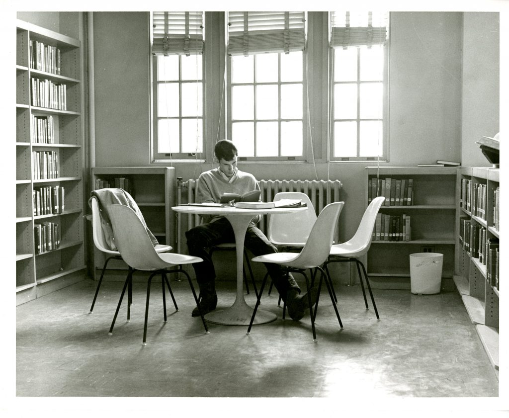 A student studies at a table in Grey Library (now Sloan Music Center) while wearing cowboy boots, 1968.
