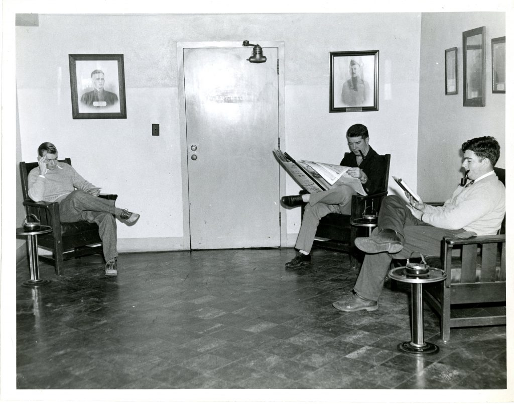 3 students read in the Grey Library smoking lounge, date unknown.