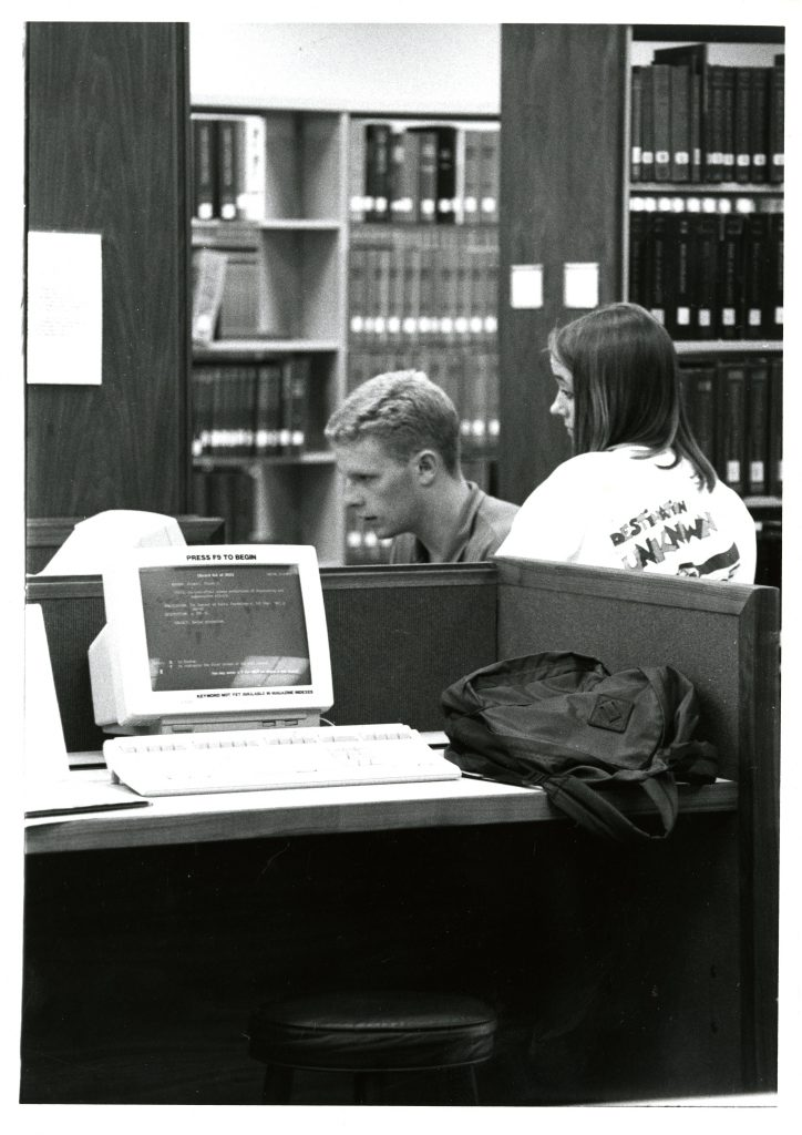 Two students use a computer in Little Library, circa 1993.