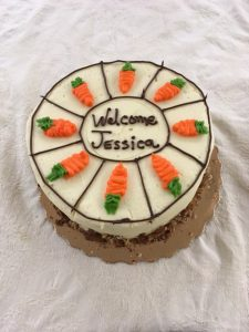 "Jessica Cottle's Welcome Cake. Carrot cake with 8 icing carrots on the top with, ""Welcom Jessica"" written on the top as well."