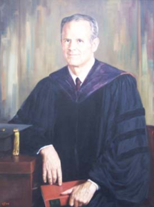 A portrait of a man in collegiate robes leans casually against his desk. His cap lies on the tabletop and he hold a bound leather book on his lap.