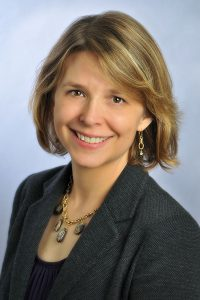 Portrait of a white business woman with short blonde hair in a gray blazer and purple blouse against a light blue background.