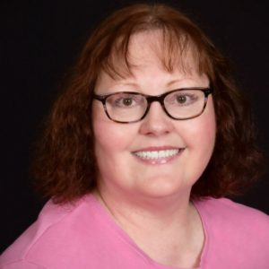 Portrait of Gillian Gremmels. Woman with black glasses, wavy brown hair with bangs and a pink blouse against a black background.