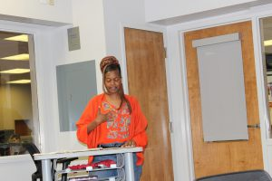 Woman stands at podium in orange shirt.