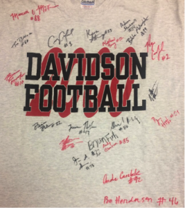 "A grey t-shirt with black and red text, reading ""Davidson Football 2000"". Perfect season. Red and black signatures of Senior football players."