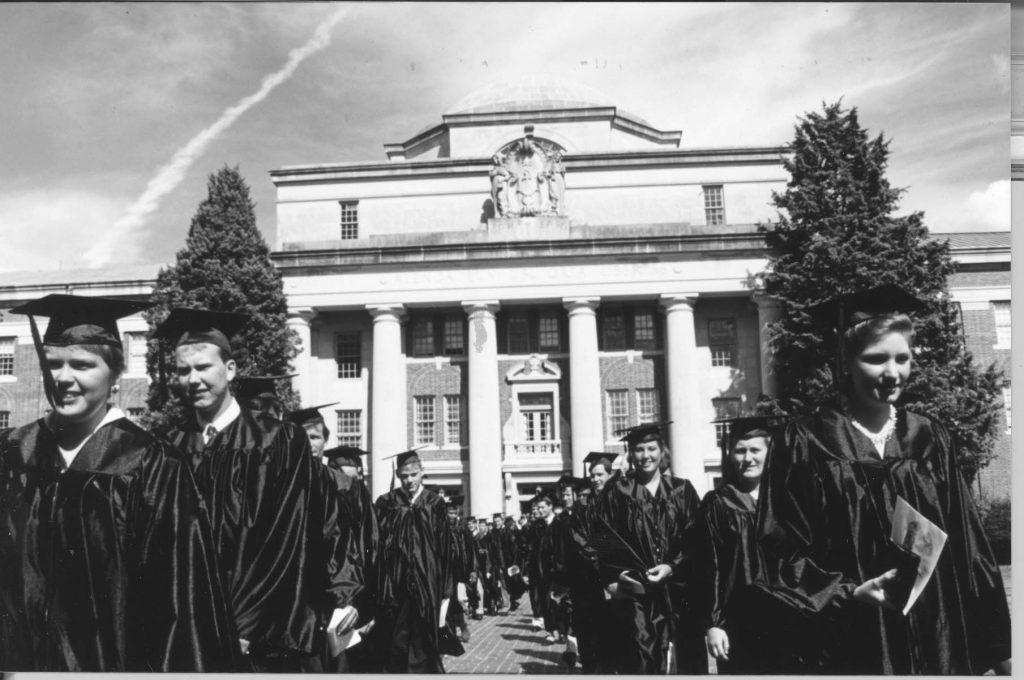 Commencement 1994. Students walk down aisle with Chambers Building in the background.