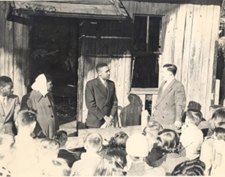 Photograph of the Lowery family meeting with Rev. Carl Prichett after the Brady's Alley fire.