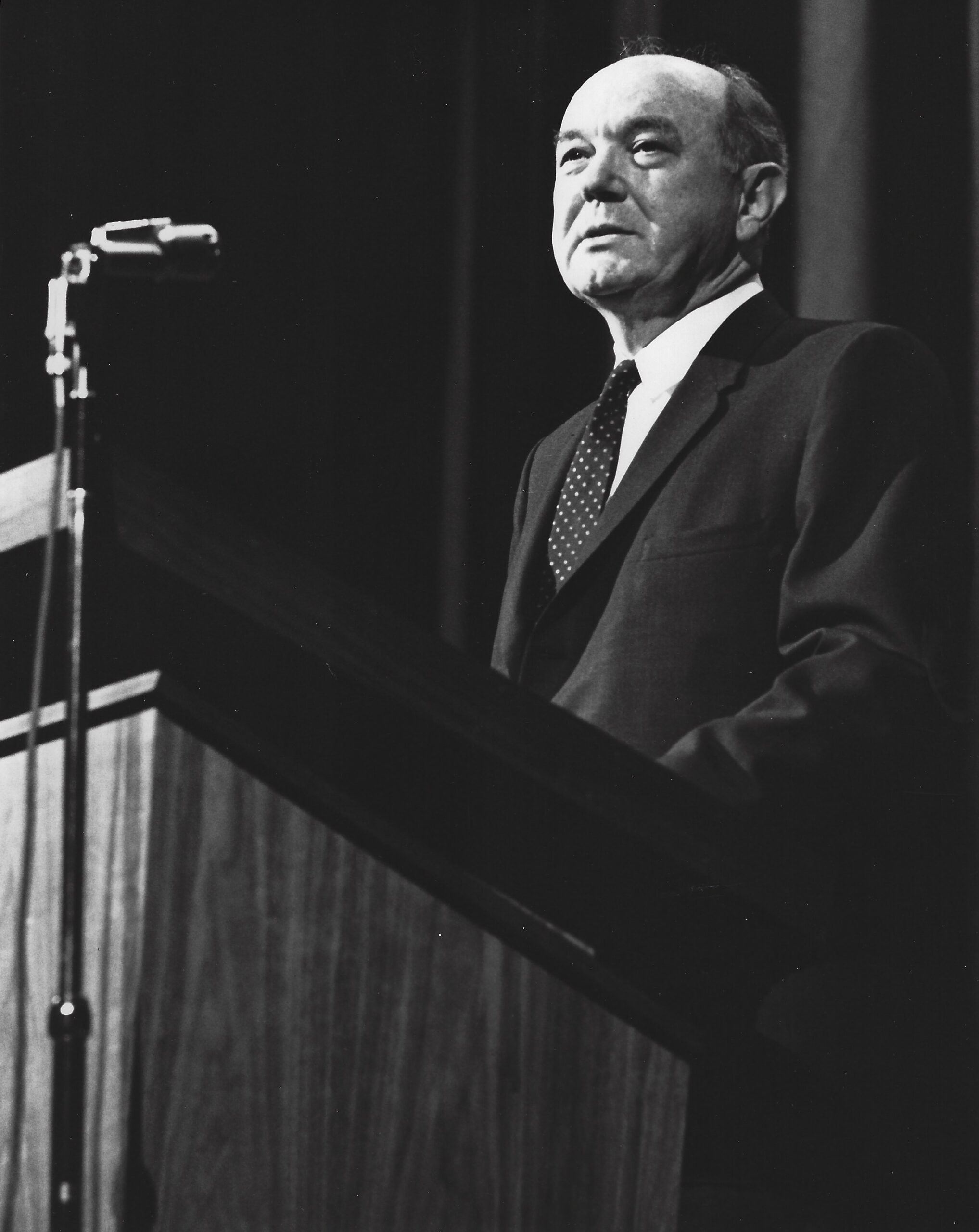 Dean Rusk standing in front of a podium