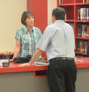Jean Coates talks with Craig Milhoan at the front desk.